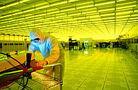 Worker testing of particle counts in clean room. Semiconductor plant