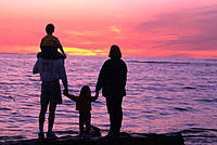 Family enjoying the beach sunset together