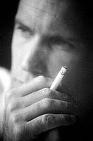 Black and white close up photograph of man holding cigarette