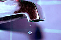 A single water drop falling from the faucet