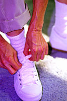 Senior woman tying shoelace