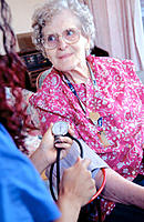 Nurse testing the blood pressure of an elderly woman