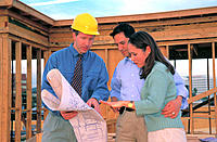 Architect discusses plans for home under construction with hispanic couple