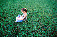 9 year old girl sitting on grass, drawing in notebook