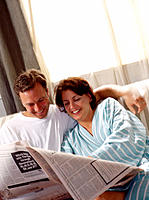 Couple at home, reading morning newspaper