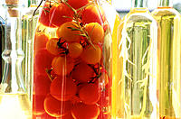Tomatoes in water and bottles of vinegar