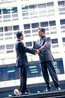Businessmen shaking hands in the street