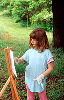 9-year-old girl painting at easel in clearing near woods, Brown County, Indiana