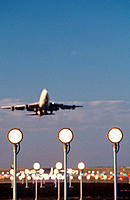 Boeing 747 taking off with runway landing lights in foreground