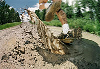 Close-up of a runners legs and feet running away through mud puddle