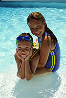 Two little girls sit in pool
