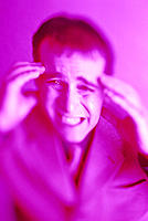 Frustrated man grabs head, purple hue