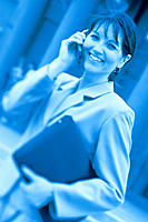 Smiling businesswoman on cell phone, blue hue