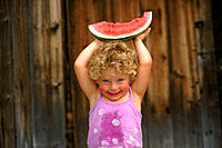 Little girl holding big piece of watermelon over her head