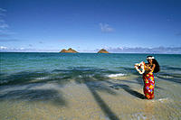 Polynesian woman on shoreline offering leis, palm shadow Mokulua Islands bkgd blue sky