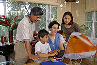 Asian American mix family at home, son on computer, everyone watching, open atmosphere