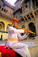 Musician playing at the courtyard of an old palace. India