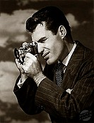 Side profile of a young man taking a photograph