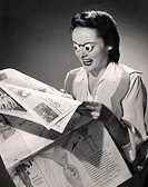 Young woman reading a newspaper with her eyes popping out