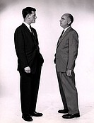 Side profile of two businessmen talking to each other