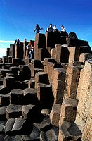 Low angle view of tourists on volcanic rocks, Giant´s Causeway, County Antrim, Northern Ireland
