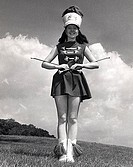 Drum majorette performing with two twirling batons and smiling
