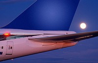 Full moon rising behind rear of Boeing 747 aircraft