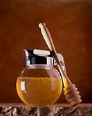 Honey in glass jug, honey spoon beside it