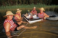 Two couples dine in water. Lake Vattern. Sweden