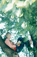 Girl reading book while sitting in tree