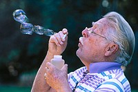 Elderly gentleman blowing bubbles