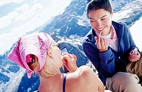 Mixed race ladies applying makeup at mountain summit. Banff NP. Canada