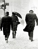 Group of people walking on a snow covered road during a blizzard, New York City, USA
