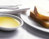 Olive oil in a small bowl and bread on a plate