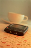 Palm Pilot, Document and Coffee Cup, Wireless Communication,/n Warm Tones