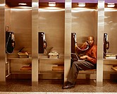 Businessman Using Pay Phone and Laptop, in Row of Phones´