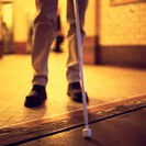CREDIT: CRISTINA PEDRAZZINI/SCIENCE PHOTO LIBRARY Blind man using a white cane (stick) to assist  in navigating a tripping hazard in his path.