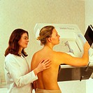 Mammography. Radiologist positioning a woman for a mammogram, an X-ray image used to screen for breast cancer or investigate breast lumps. The breast ...