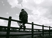 CREDIT: MARTIN RIEDL/SCIENCE PHOTO LIBRARY Man outdoors sitting on a fence.