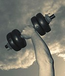 CREDIT: MIKE BLUESTONE/SCIENCE PHOTO LIBRARY Dumb-bell.  Dumb-bell lifted up  against  the  sky during a workout.