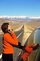 Woman on cell phone outside car at desert highway. Nevada. USA