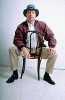 Man, 40-45, looking at camera while sitting on chair
