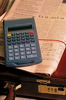 Calculator, briefcase and newspaper
