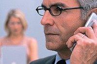 Businessman talking on cell phone, businesswoman in the background, blurred
