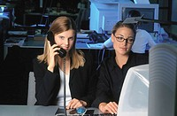 Two businesswomen in front of computer, businesswoman talking on phone