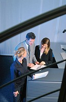 Three businesspeople looking on files