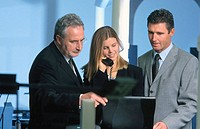 Three businesspeople, businesswoman talking on phone