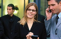Businesswoman looking at camera, businessman talking on cell phone