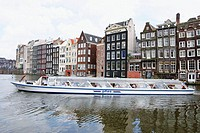Canal tour boat at Damrak. Amsterdam. Holland