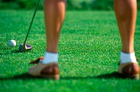 Detail of a female golfer about to hit a drive